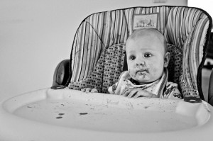 Black and white photo of a baby sitting in a high chair with food on its face