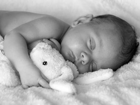 Black and white photo of a baby asleep with cuddly toy rabbit